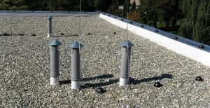 Photo of commercial flat roofing system with rocks on roof