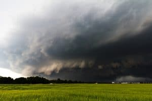 Dark cloud that could produce hail storms passes over a grassy field