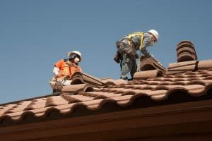 Two roofers install clay tiles on a roof