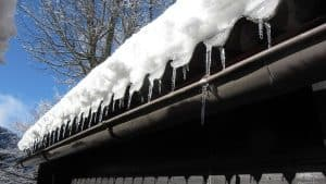 A roof in winter with snow and icicles