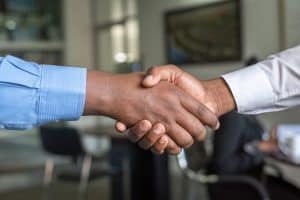Two men shaking hands agreeing to do business with Elite Roofing.